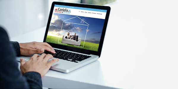 person looking at a laptop with Caniglia Heating & Cooling website