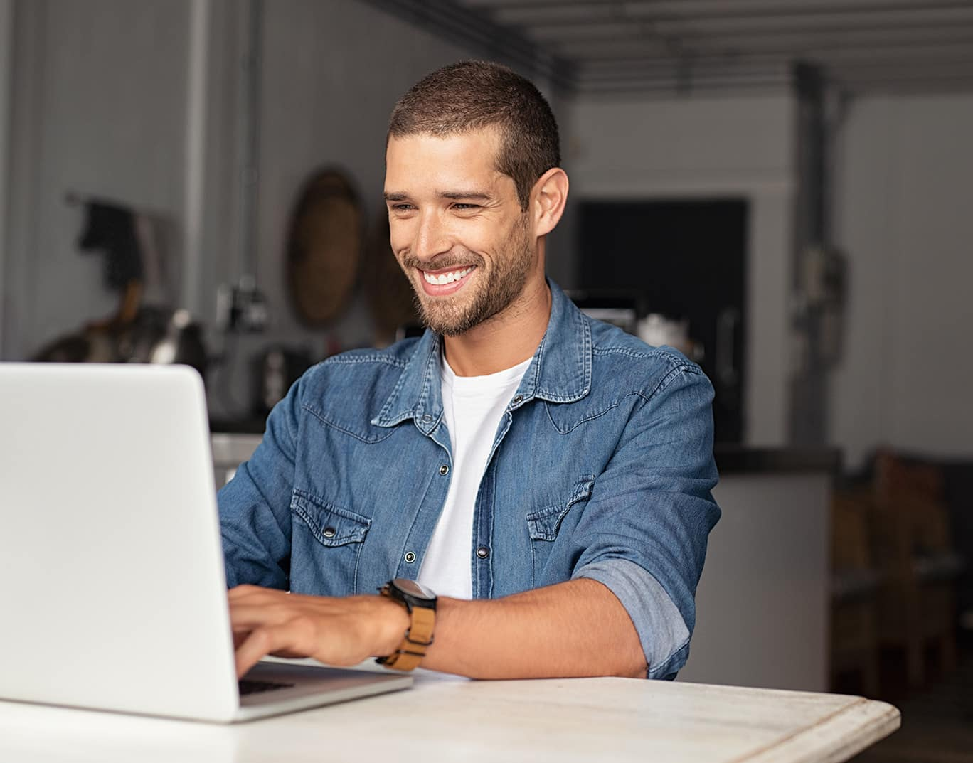 Man smiling at laptop computer