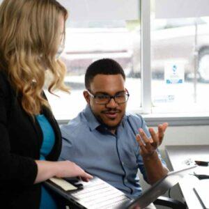 Lynn and Jonathan talking while looking at laptop